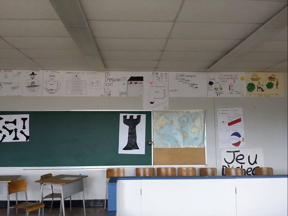 Une classe du secondaire avec plein de dessins sur le mur